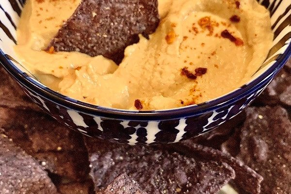 Sunflower seed queso dip with blue corn tortilla chips
